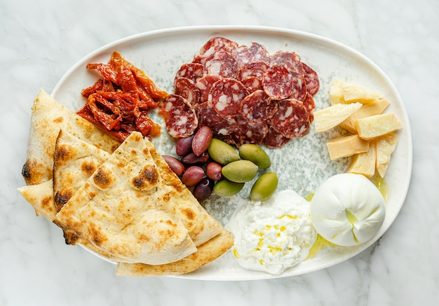 Antipasto platter with different cheese, meat and focaccia on marble surface