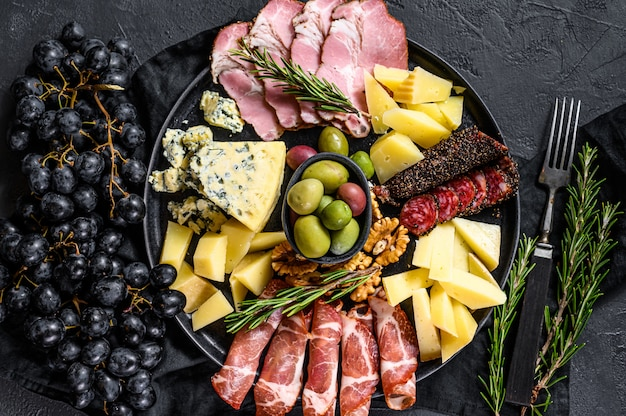 ハム、生ハム、サラミ、ブルーチーズ、モッツァレラチーズ、オリーブの前菜盛り合わせ。黒の背景。上面図