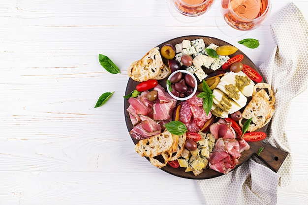 Antipasto platter with ham, prosciutto, salami, blue cheese, mozzarella with pesto and olives. top view, overhead