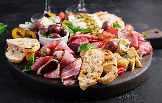 Antipasto platter with ham, prosciutto, salami, blue cheese, mozzarella with pesto and olives.