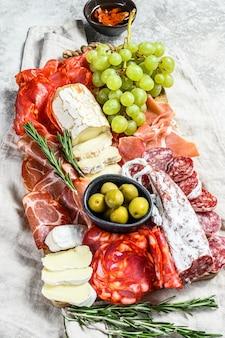 Антипасто подать блюдо. мясо холодного копчения с колбасой, ломтиками ветчины, ветчиной, беконом, оливками. разнообразие закусок. серая поверхность. вид сверху