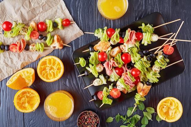 鶏肉、生ズッキーニ、チェリートマト、モッツァレラボール、サラミスライス、ガラスカップにオレンジジュースを入れた木製テーブルのプレートにオリーブを添えた前菜の串焼き、上からの眺め、フラットレイ