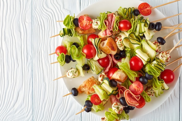 Antipasto skewers with grilled chicken meat, raw zucchini ribbons, tomatoes, seasoned mozzarella balls, salami slices, black olives on a white plate on a wooden table, view from above