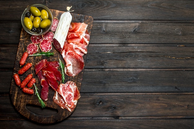 Antipasto surface. assortment of meat snacks on the board with olives and parmesan. on a wooden surface.