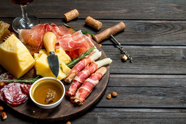 Antipasto surface.board with traditional italian snacks. on a wooden surface.