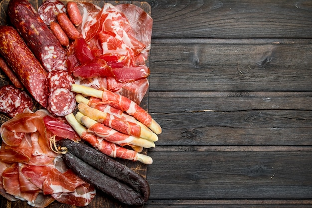 Antipasto surface.a variety of meat snacks. on a wooden surface.