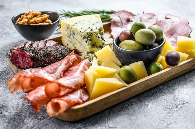 前菜各種前菜、生ハム、サラミ、コッパ、チーズ、オリーブのまな板。灰色の背景。上面図