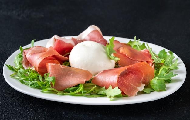 Антипасто с прошутто, моцареллой и свежей рукколой на сервировочной тарелке