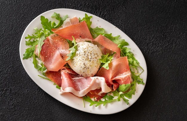 Antipasto with prosciutto , mozzarella and fresh arugula on the serving plate