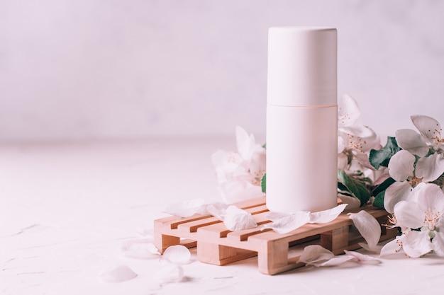 Шариковый дезодорант-антиперспирант на деревянном подиуме в виде поддона на светлой штукатурке с цветами яблони. копировать пространство