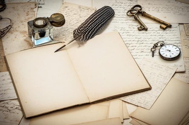 골동품 액세서리, 오래된 편지, 잉크병 및 빈티지 깃털 잉크 펜. 향수를 불러일으키는 감상적인 종이 배경. 선택적 초점