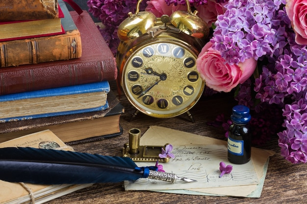 Antique alarm clock, pile of mail with blue feather pen and flowers