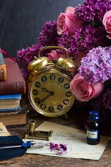 Antique alarm clock, pile of mail with blue feather pen