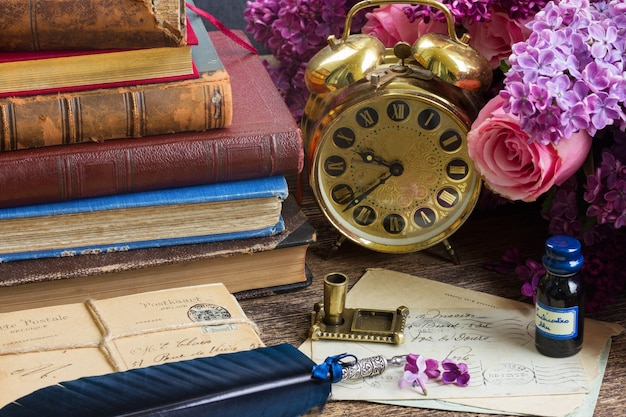 Antique alarm clock, pile of mail with blue quill pen and flowers