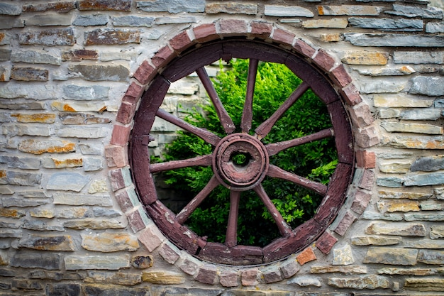 Античное и выдержанное деревянное колесо фургона тележки в старой каменной стене здания фермы.