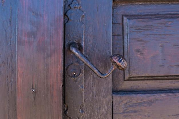 금속으로 만든 열쇠 구멍이있는 골동품 검은 손잡이가 그려진 나무 문에 붙어 있습니다.