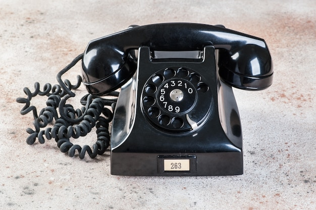 Antique black rotary phone on concrete background.