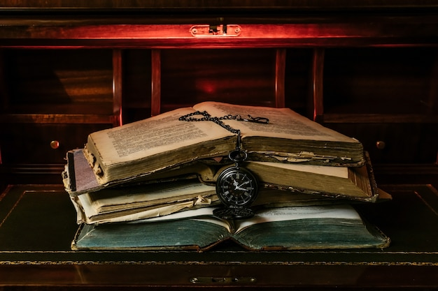 Antique books stacked with a pocket watch