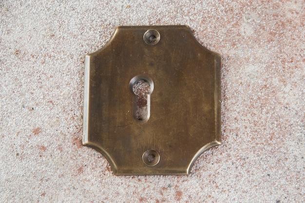 콘크리트에 골동품 황동 열쇠 구멍 덮개