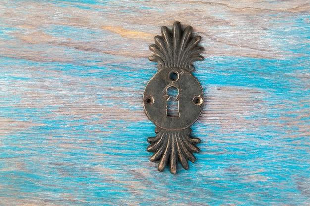 青い木製の背景にアンティーク真鍮の鍵穴ロックカバー。テキスト用のスペースをコピーします。