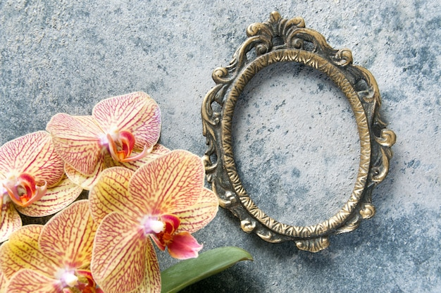 Antique brass picture frame and orchid flowers