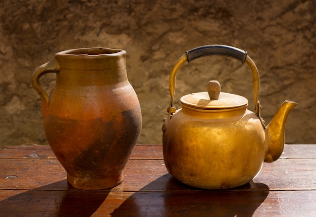 Antique brass teapot on retro wood table and clay jar