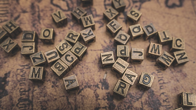 Antique bronze alphabets on old world map