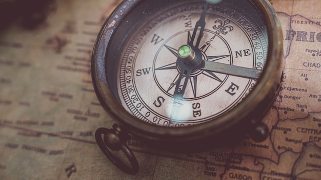 Antique bronze compass on old world map