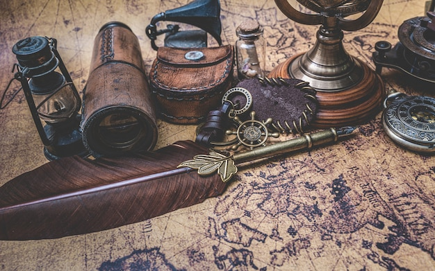 Antique bronze quill pen and old collection on old world map
