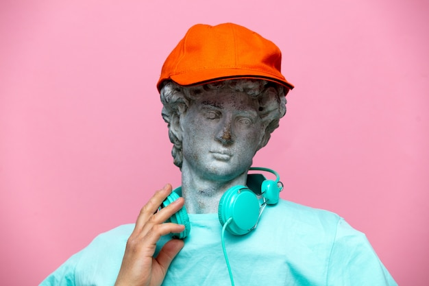 Antique bust of male in cap with headphones on pink background.
