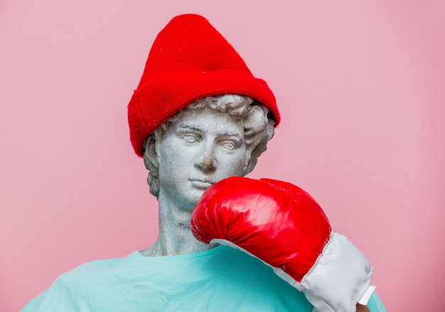 Antique bust of male in hat with boxing glove on pink background