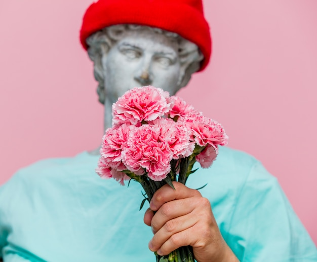 Antique bust of male in hat with carnations bouquet