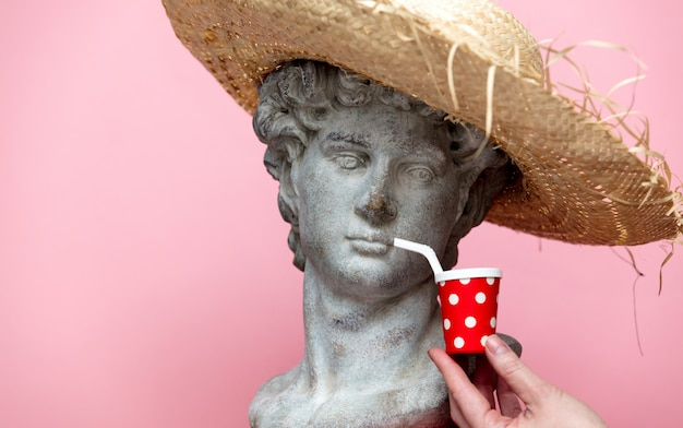 Antique bust of male in hat with cola drink on pink background.
