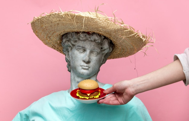 Antique bust of male in hat with hamburger on pink background