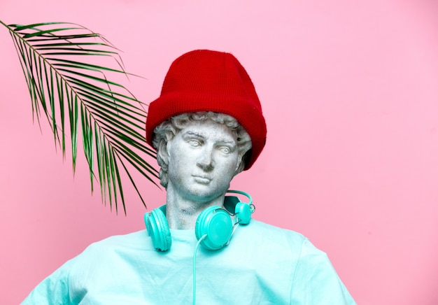 Antique bust of male in hat with headphones on pink background.