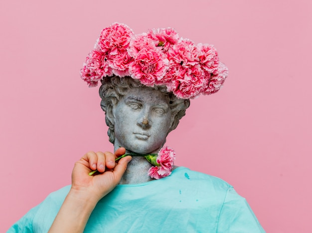 Antique bust of male with carnations bouquet in a hat