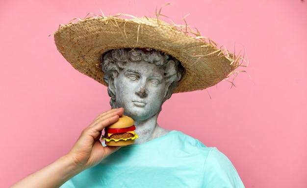 Античный бюст мужчины в шляпе с гамбургером на розовом фоне