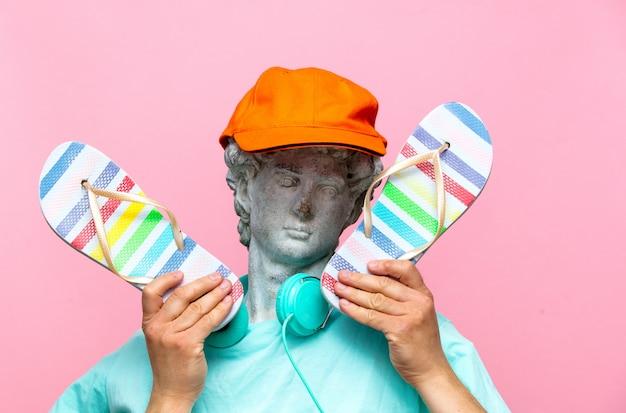 Античный бюст мужчины в шляпе с наушниками и шлепанцы