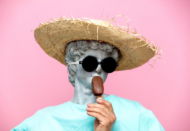 Античный бюст мужчины в шляпе с мороженым на розовом фоне.