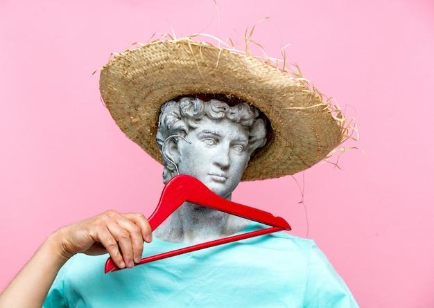 Античный бюст мужчины в шляпе с красной вешалкой