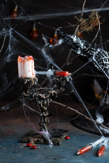 Antique candelabra with melting candle, spider web and a syringe with tomato juice on black
