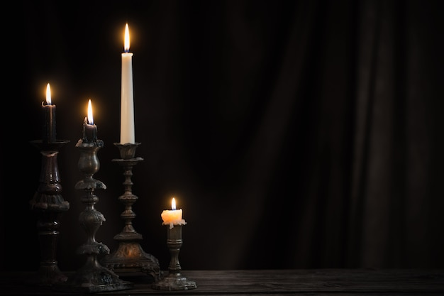 Antique candlestick with burning candle on old wooden table on background black velvet curtain
