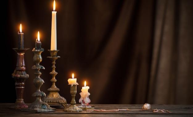 Античный подсвечник с горящей свечой на старом деревянном столе на фоне коричневого бархатного занавеса