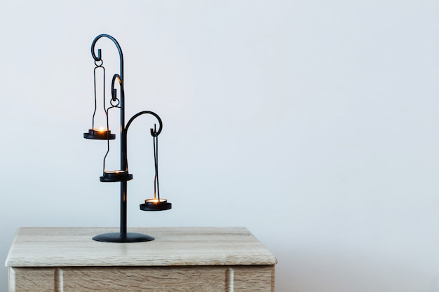 Antique candlestick with burning candles on background white wall