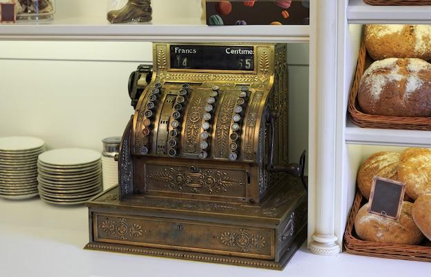 Старинный кассовый аппарат на витрине магазина