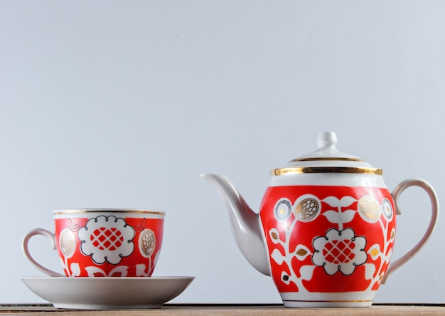 Antique ceramic cup and teapot on wooden table against a white wall