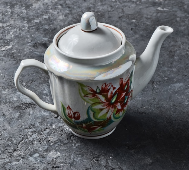 An antique ceramic teapot close-up with patterns on a black concrete table.