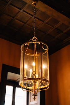 Antique chandelier with five candles in a glass bulb