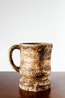 Antique clay cup on wooden table and white surface