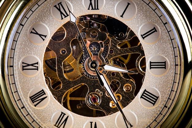 ヴィンテージ本の背景にアンティークの時計。チェーンの機械式時計仕掛け。